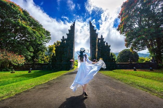 Mulher caminhando no grande portão de entrada, bali, na indonésia