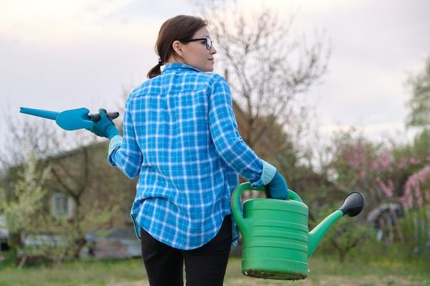 Mulher caminhando no jardim na primavera, vista traseira. jardineira segurando um regador e ferramentas de jardim