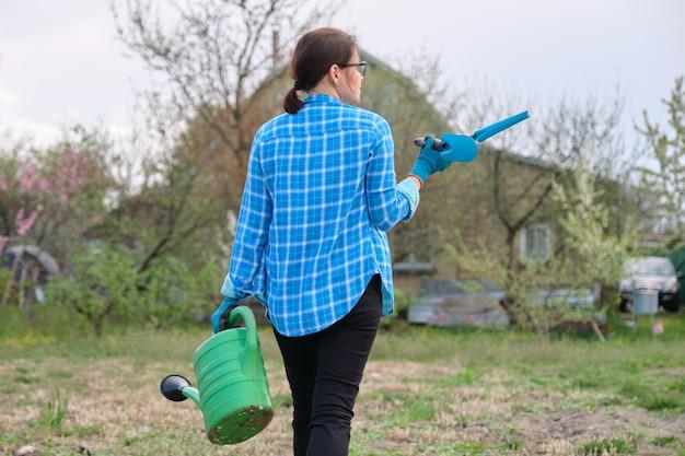 Mulher caminhando no jardim na primavera