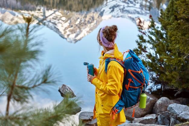 Mulher caminhando para perto de um lago nas montanhas, carrega as costas, segura uma garrafa térmica com bebida quente, explora algo novo