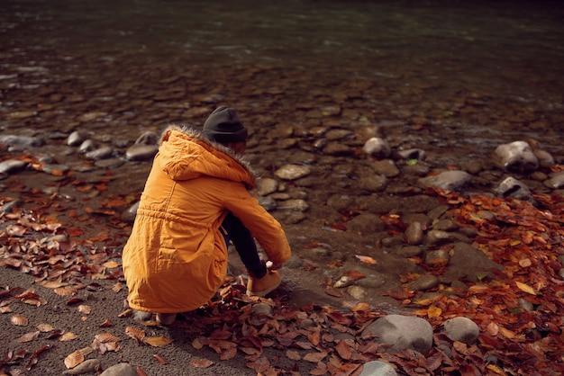 Mulher caminhando perto do rio caída, deixando montanhas naturais