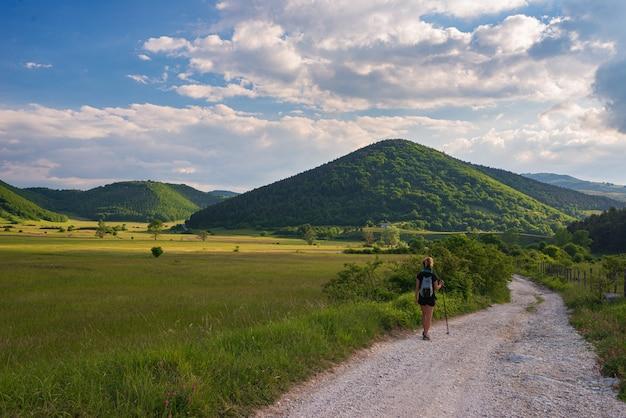 Mulher caminhando por uma estrada de terra em uma paisagem rural