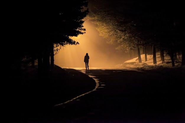 Mulher caminhando sozinha na estrada enevoada e enevoada em uma cena mística dramática com cores quentes