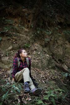 Mulher caminhante na floresta tomando um descanso sentando cachoeira próxima desfrutar com a natureza.