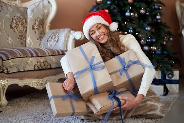 Mulher camisola branca chapéu de papai noel sentado no chão perto da árvore de natal enrolou-se cobertor. branco feminino inverno casa interior de férias com caixa de presente aberta xadrez ganância muitos presentes
