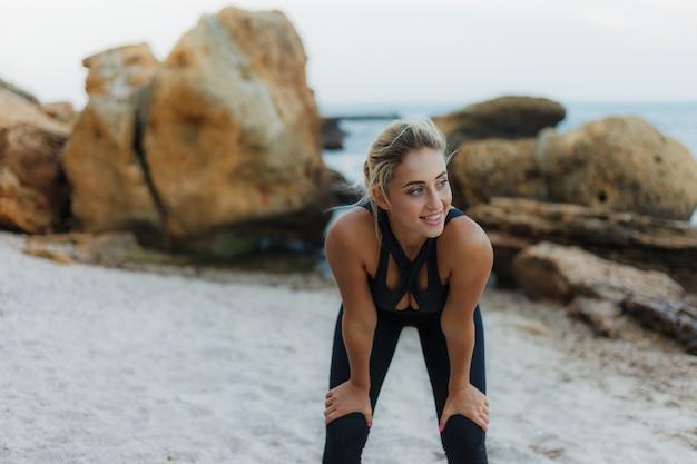Mulher cansada aptidão atraente no sportswear em uma praia selvagem.