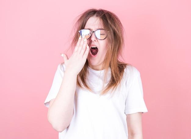 Mulher cansada bocejando, cobrindo a boca aberta com a mão precisa de descanso. uma jovem trabalhadora com uma cabeça sonolenta não consegue acordar com insônia.