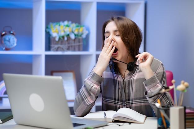 Mulher cansada bocejando, sentado à mesa com o laptop, estudante preguiçoso fazendo lição de casa, preparando-se para passar no exame, menina com sono, trabalhando no computador após a noite sem dormir, falta de conceito de sono e tédio