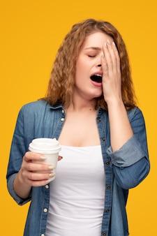 Mulher cansada com café para ir bocejar
