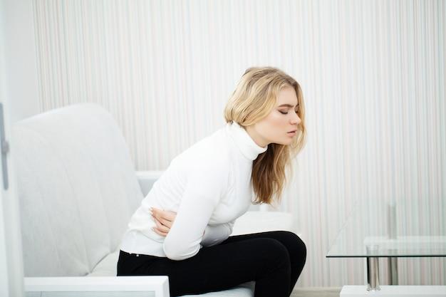 Mulher cansada com dor de estômago sentado no sofá