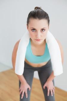 Mulher cansada com toalha em volta do pescoço no estúdio de ginástica