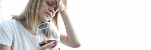 Mulher cansada com um copo de vinho tinto na cabeça