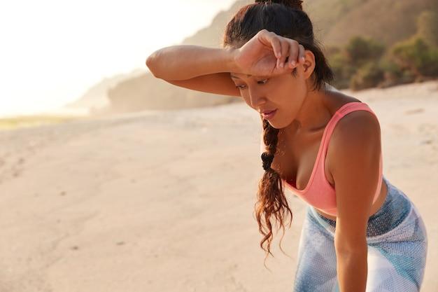Mulher cansada com um pano úmido na testa após intenso treinamento físico