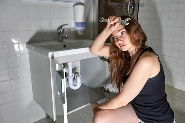 Mulher cansada com uma chave inglesa sentada em frente ao sifão embaixo da pia do banheiro