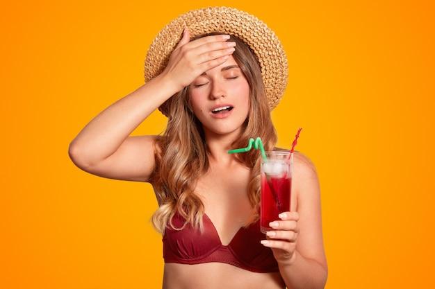 Mulher cansada de biquíni e chapéu de verão, mantém a mão na testa, tem dor de cabeça depois de estar ao ar livre durante condições climáticas quentes e abafadas