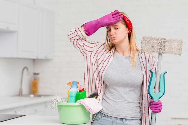 Mulher cansada de limpar em casa