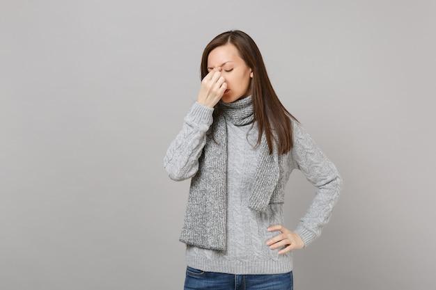Mulher cansada de suéter cinza, lenço, mantendo os olhos fechados, colocando a mão no rosto isolado em fundo cinza. estilo de vida de moda saudável, emoções sinceras de pessoas, conceito de estação fria. simule o espaço da cópia.