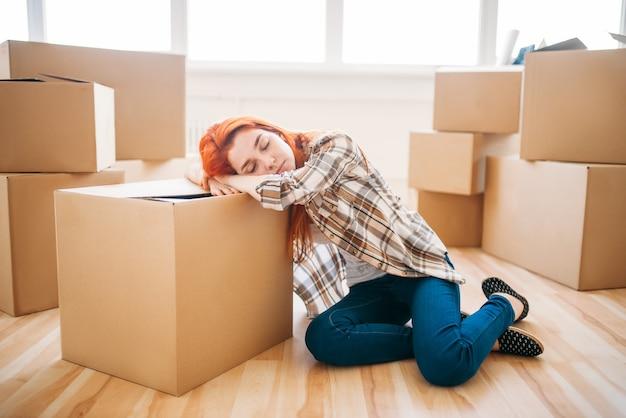 Mulher cansada dorme na caixa de papelão, inauguração de casa. mudança para uma nova casa