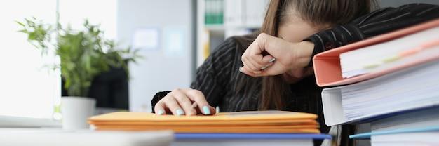 Mulher cansada dormindo em documentos em papel no escritório