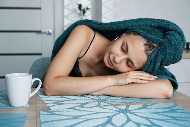 Mulher cansada dormindo na mesa. linda garota com uma toalha no cabelo se senta com uma xícara de café. manhã preguiçosa e sonolenta