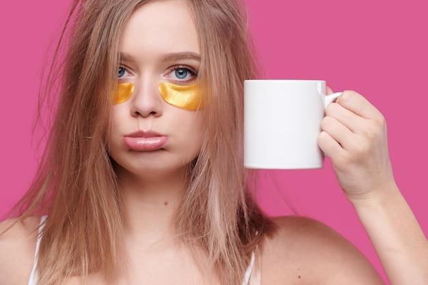 Mulher cansada e bêbada com ressaca pôs manchas nos olhos segurando uma xícara de café branco