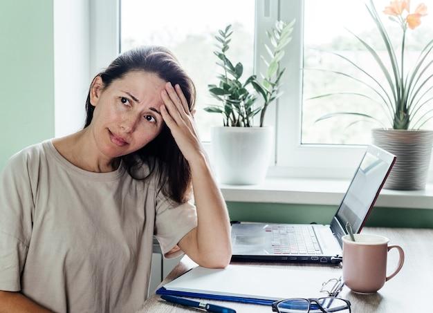 Mulher cansada e estressada, sofrendo de dor de cabeça, trabalhando em casa, sentada à mesa