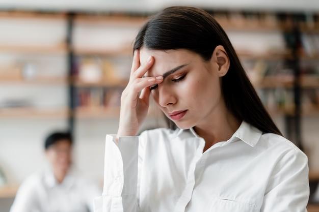 Mulher cansada e exausta, segurando a cabeça no escritório