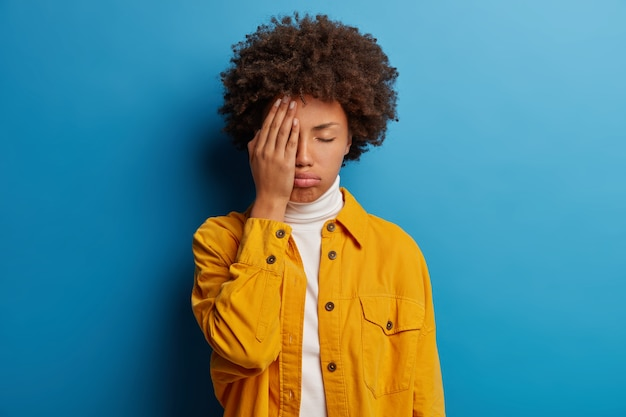 Mulher cansada e farta cobre metade do rosto, mantém os olhos fechados, suspira de cansaço, sente-se exausta para trabalhar sem descansar, posa em estúdio contra uma parede azul