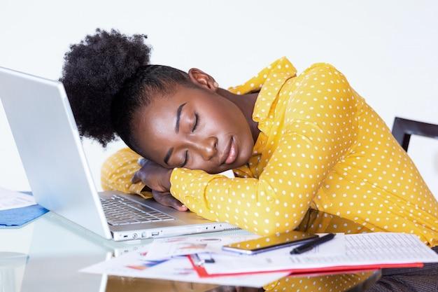 Mulher cansada e sobrecarregada, descansando enquanto trabalhava escrevendo notas