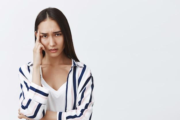 Mulher cansada e sombria com belos cabelos longos em uma blusa listrada, tocando a têmpora e olhando confusa