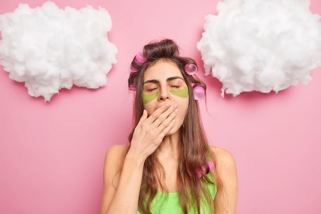 Mulher cansada e sonolenta boceja e cobre a boca, estando exausta de terapias de beleza, aplica rolos de cabelo e adesivos de hidrogel verdes sob os olhos isolados sobre a parede rosa