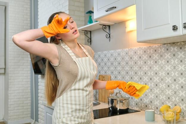 Mulher cansada em luvas de avental fazendo limpeza de casa na cozinha