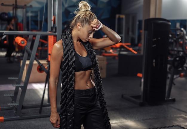 Mulher cansada esporte no sportswear com corda de batalha no pescoço no ginásio. treino funcional. conceito de estilo de vida saudável
