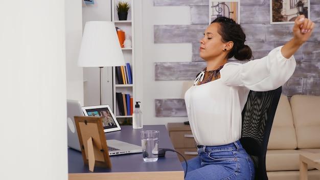 Mulher cansada no escritório em casa, esticando as costas.