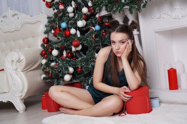 Mulher cansada perto de caixas de presente e árvore de natal em um interior branco