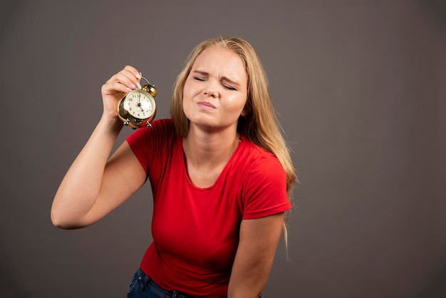 Mulher cansada, segurando o relógio em fundo escuro. foto de alta qualidade
