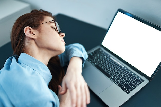 Mulher cansada sentada à mesa em frente a um laptop insatisfeita com o trabalho