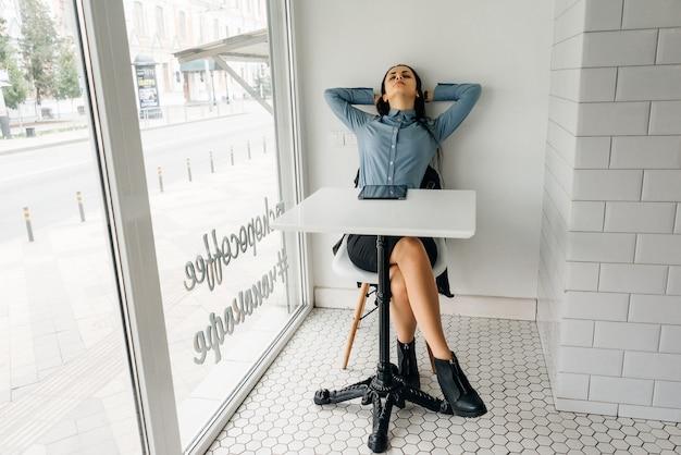 Mulher cansada sentada à mesa em frente a uma grande janela