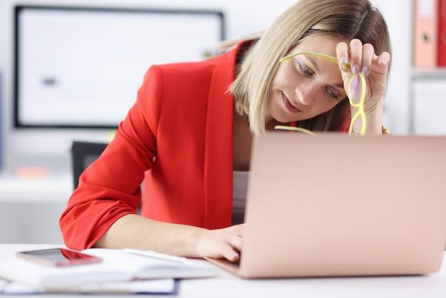 Mulher cansada sentada no laptop com óculos nas mãos