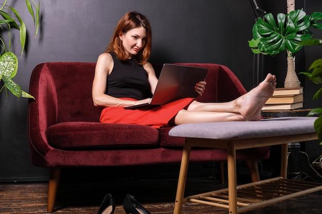 Mulher cansada tirou os sapatos, colocou os pés na mesinha de centro e navegou na internet