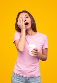 Mulher cansada tomando uma xícara de café para bocejar e esfregar o rosto contra um fundo amarelo pela manhã
