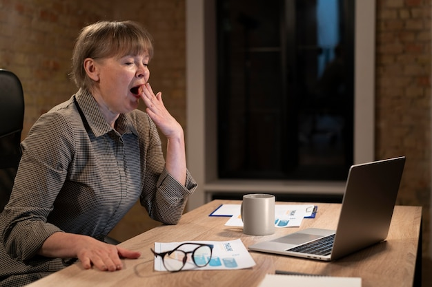 Mulher cansada trabalhando até tarde em um prazo