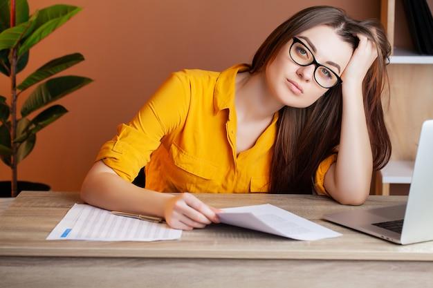 Mulher cansada, trabalhando no computador no escritório