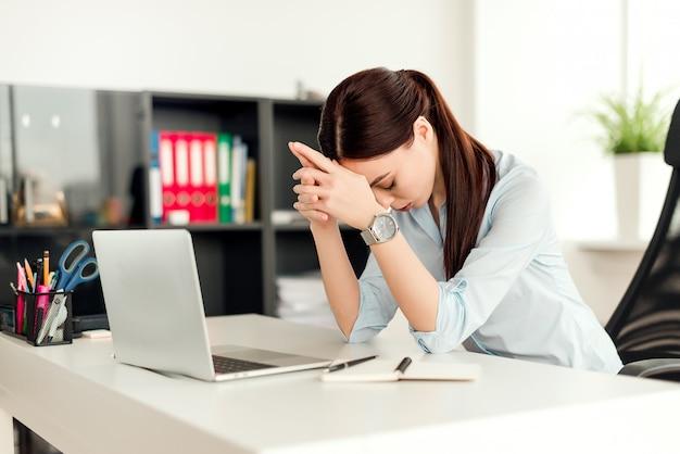 Mulher cansada, trabalhando no escritório no seu local de trabalho