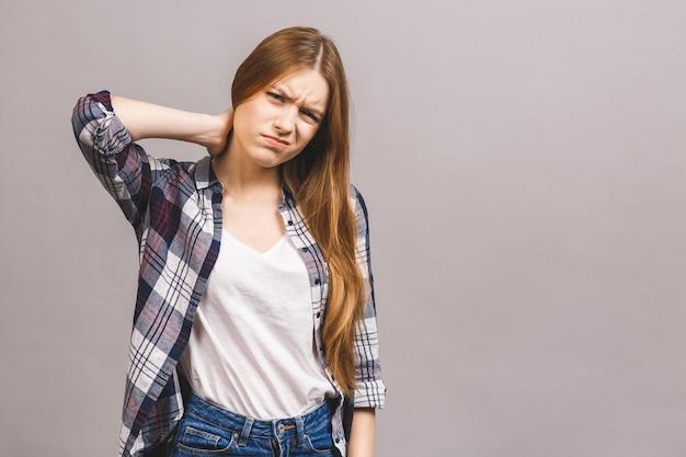 Mulher cansado que tem a bandeja no pescoço isolada contra a parede cinzenta.