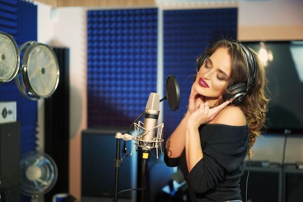 Mulher cantando em um estúdio de gravação.