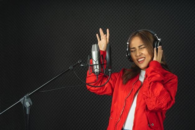 Mulher cantora asiática em um estúdio de gravação usando um microfone de estúdio com paixão em um estúdio de gravação de música
