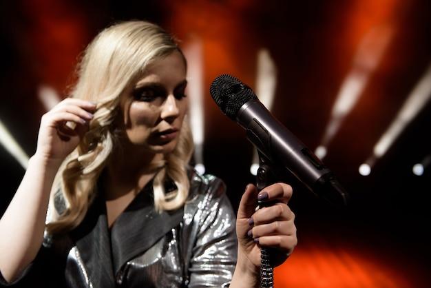 Mulher cantora no palco. cantor e microfone.