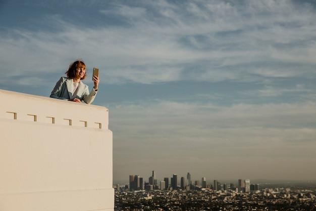 Mulher capturando a vista de los angeles com seu telefone no observatório griffith, eua