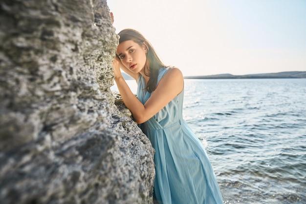 Mulher carinhosa em vestido azul posando na baía de bakota